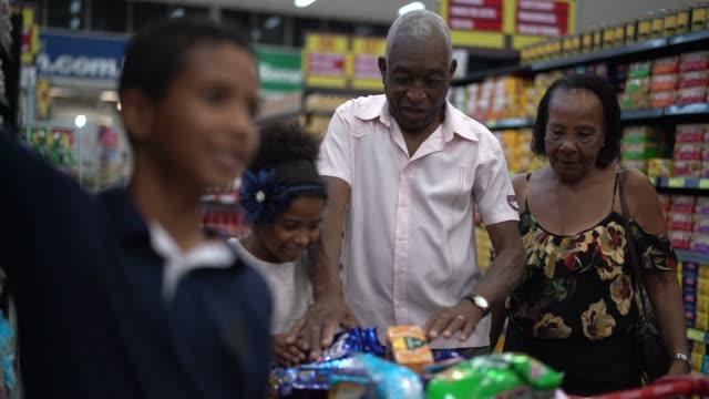 vídeos y material grabado en eventos de stock de familia afro hispano latino compra en supermercado - snack aisle