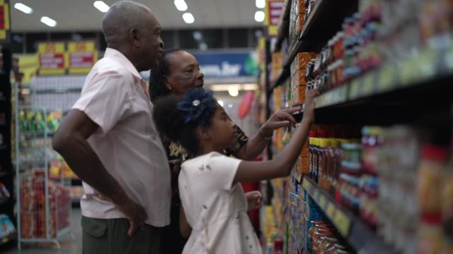 Afro Hispanic Latino family buying on supermarket Family on Supermarket snack stock videos & royalty-free footage