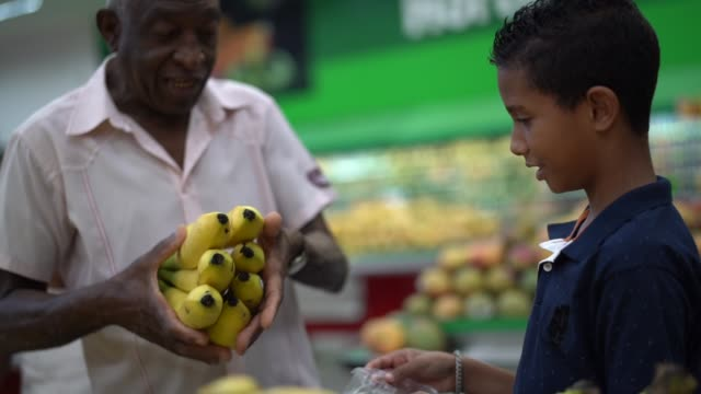 Afro Hispanic Latino Grandchild and grandfather buying on supermarket Family on Supermarket banana stock videos & royalty-free footage