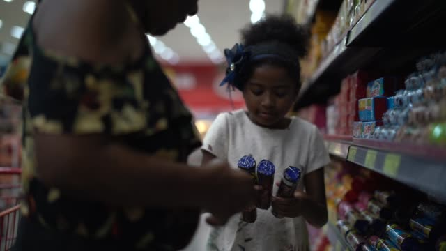 Afro Hispanic Latino Granddaughter and grandmother buying on supermarket Family on Supermarket snack aisle stock videos & royalty-free footage