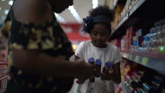 vídeos y material grabado en eventos de stock de los hispanos latinos nieta y abuela comprando en el supermercado - snack aisle