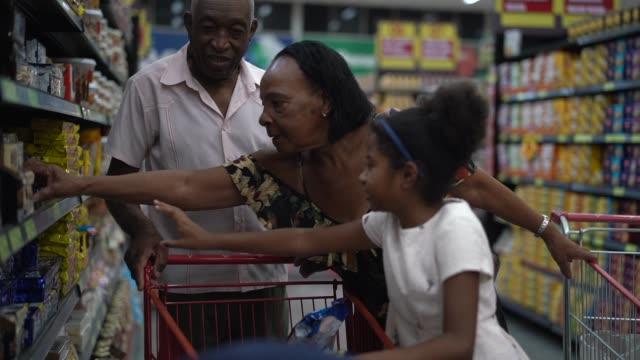 vídeos y material grabado en eventos de stock de los hispanos latinos nieta y abuelos comprando en el supermercado - snack aisle