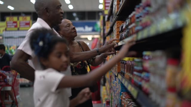 Afro Hispanic Latino Granddaughter and Grandparents buying on supermarket Family on Supermarket snack aisle stock videos & royalty-free footage