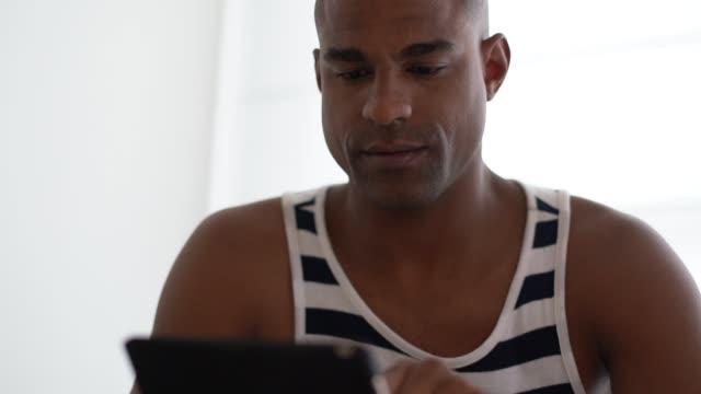 афро латинский человек с помощью планшета на диване - бразилец парду стоковые видео и кадры b-roll