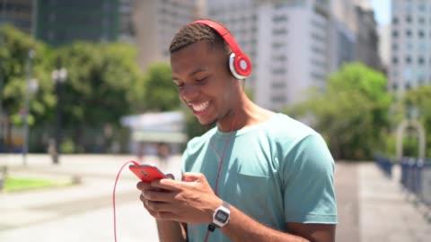 vidéos et rushes de afro latin à l'aide de mobile et écoute de la musique dans la ville - insouciance