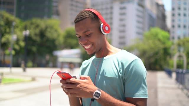 afro latin använder mobila och lyssna musik i staden - bekymmerslös bildbanksvideor och videomaterial från bakom kulisserna