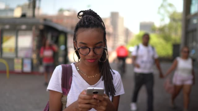 Afro latin young woman in the city using smartphone portrait