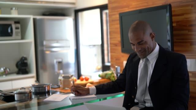 uomo d'affari afro latino che lavora su un laptop a casa - to do list video stock e b–roll