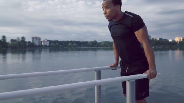 Afro man doing triceps dips on parallel bars near lake