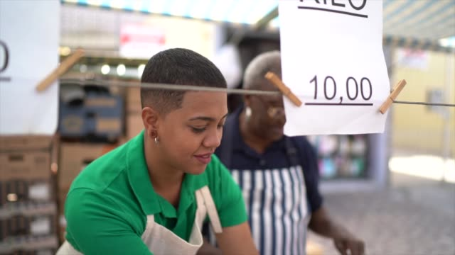 afro mother and daughter woman working in a street market - family business - cultura latino americana video stock e b–roll