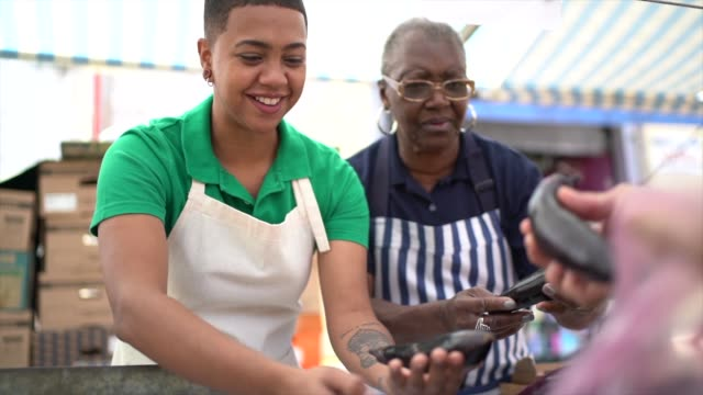 afro mother and daughter woman working in a street market - family business - video di bancarella video stock e b–roll