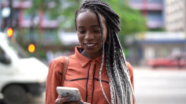 afro woman using mobile at street - capelli neri video stock e b–roll