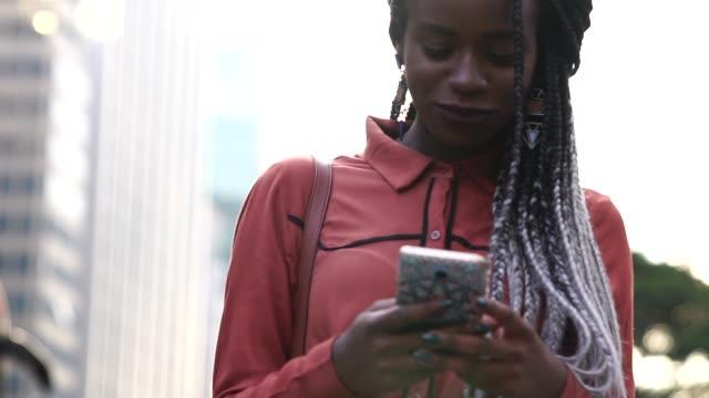 stockvideo's en b-roll-footage met afro vrouw lopen en het gebruik van mobiele in city - business woman phone