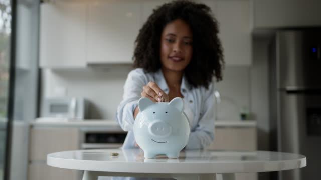 vídeos de stock e filmes b-roll de afro young woman inserting coins into her piggy bank - economia