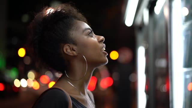vídeos de stock e filmes b-roll de afro young woman looking for the news at newsstand - elegante
