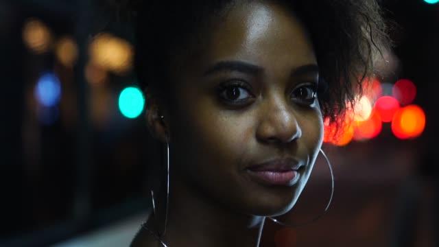 vídeos de stock, filmes e b-roll de retrato de mulher jovem afro na cidade à noite - brasileiro pardo