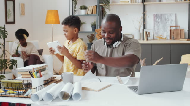Afro-American Architect Working at Home and Helping Little Son with Tablet