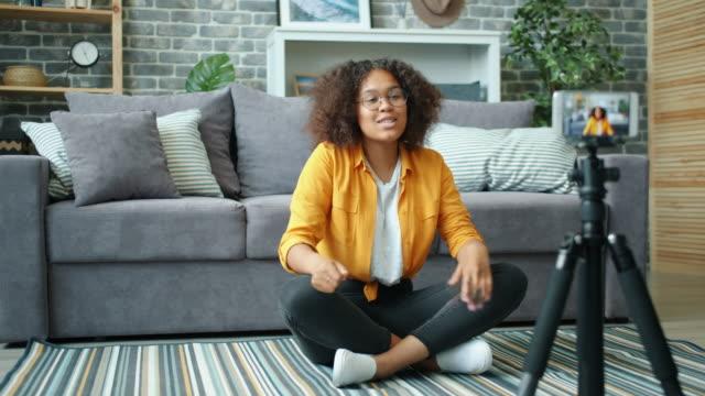 아프로 - 미국 블로거는 스마트 폰으로 엄지 손가락을 보여주는 동영상 블로그에 대한 비디오를 녹화 - influencer 스톡 비디오 및 b-롤 화면