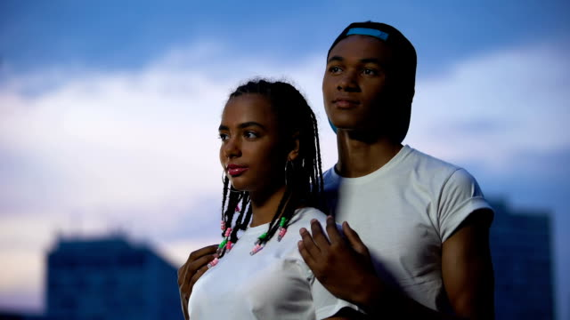 vídeos de stock e filmes b-roll de afro-american couple embracing against evening sky, supportive relationships - future hug