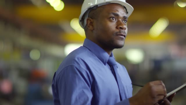 Afro-American employee filling out checklist Chest-up shot of Afro-American warehouse employee wearing safety helmet, blue shirt and tie, filling out checklist on clipboard, against blurred dimly lit background occupational safety and health stock videos & royalty-free footage