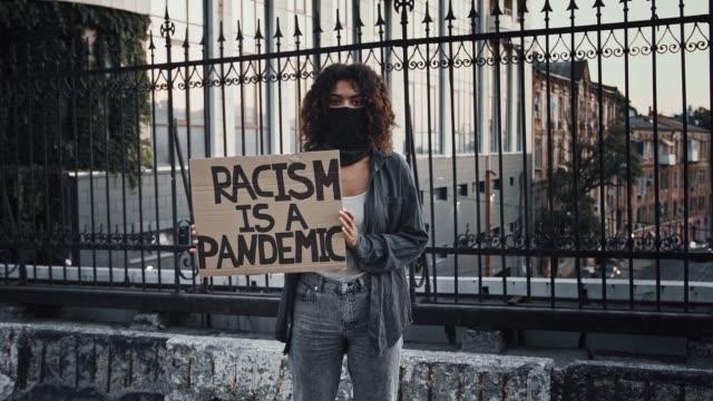 afro-amerikansk kvinna i svart bandana i ansiktet. visar kartong affisch med inskription rasism är en pandemi. står på bryggan. protester i usa - etnicitet bildbanksvideor och videomaterial från bakom kulisserna
