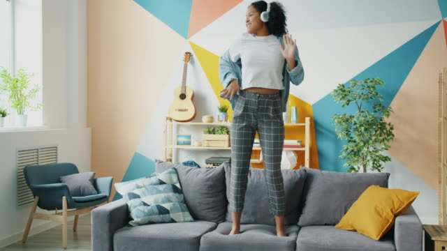 Afro-American girl in headphones dancing on sofa listening to music having fun Afro-American girl in headphones dancing on sofa listening to music having fun in apartment alone. Happy people, modern lifestyle and millennials concept. student life stock videos & royalty-free footage