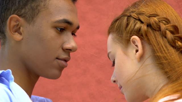 afro-american guy preparing to kiss beautiful teenage female, romantic date - kids kiss embarrassed video stock e b–roll