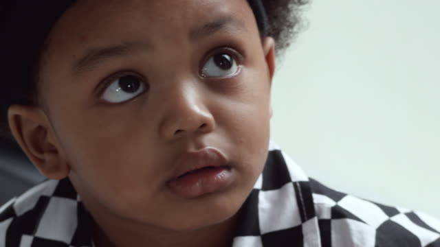 afro-american kid looking up and thinking - soltanto neonati video stock e b–roll