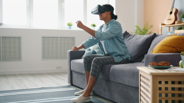 Afro-American lady in vr glasses is enjoying driving game at home moving arms and legs