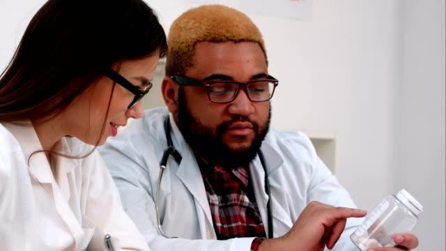 vidéos et rushes de médecin de sexe masculin afro-américaines tenant le bocal de pilules en infirmière, prendre des notes - pots de bureau