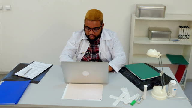 Afroamerican male doctor working in the office when the light turns off