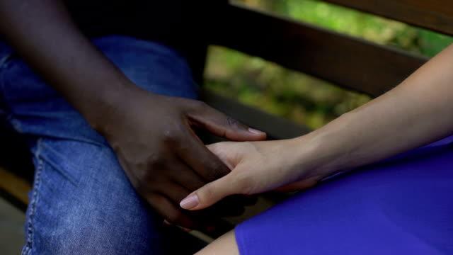 afro-american male holding female hand, multiracial love, stereotype, closeup - mano donna dita unite video stock e b–roll