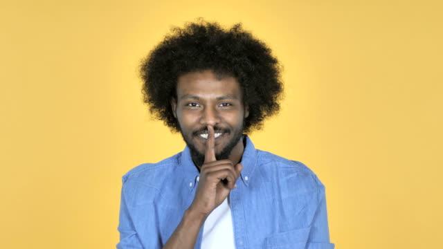 afro-american man gesturing silence, finger on lips, yellow background - cisza filmów i materiałów b-roll