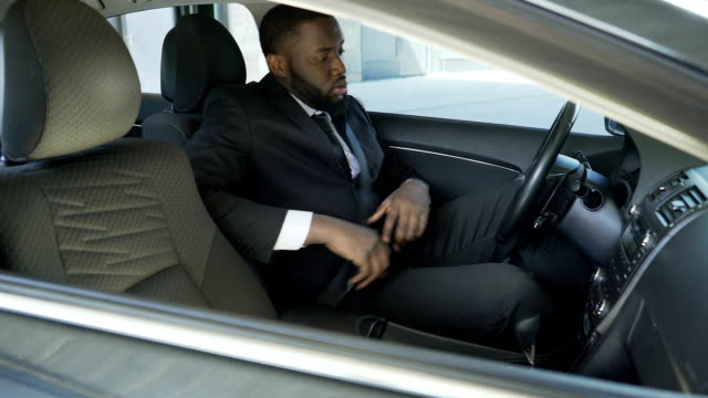 Afro-American man in expensive suit fastening and turning on ignition of his car video