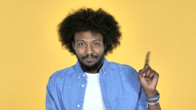 afro-amerikanischer mann winken finger zu verweigern auf gelbem hintergrund - ekel stock-videos und b-roll-filmmaterial