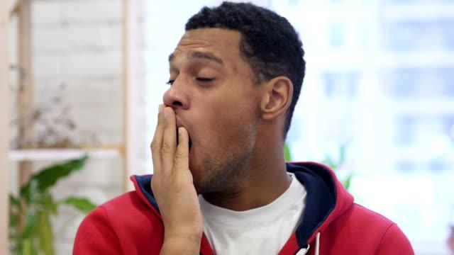 afro-american man yawning in office - nuda filmów i materiałów b-roll