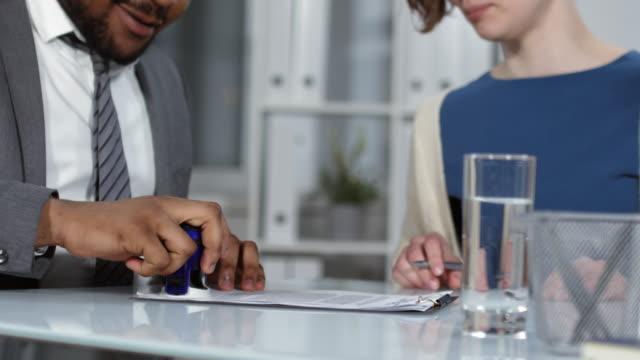 vidéos et rushes de accord de témoin de notaire afro-américain pour le couple de clients - notaire
