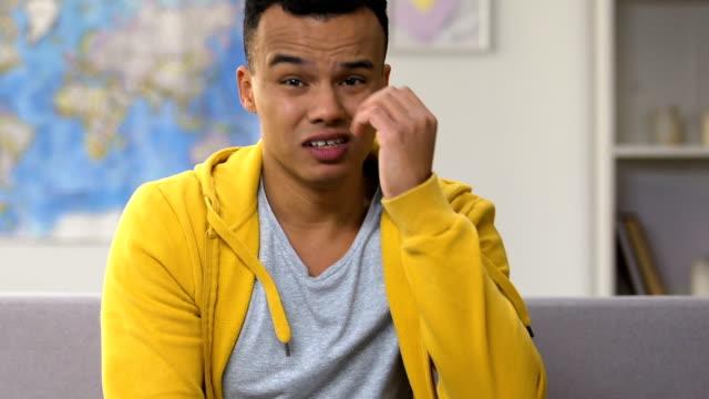 vídeos de stock e filmes b-roll de afro-american teenager feeling upset with favorite sports team losing playoffs - criança perdida