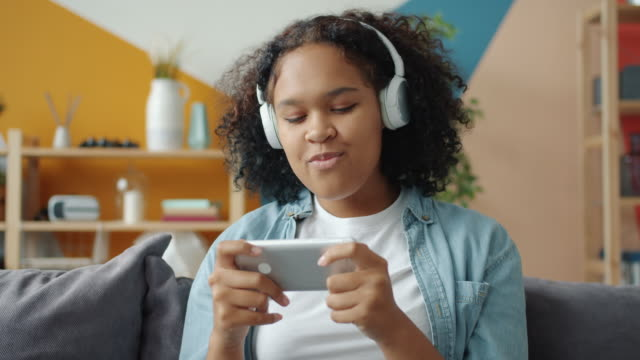 afro-american teenager playing smartphone game and listening to music at home - cuffie wireless video stock e b–roll