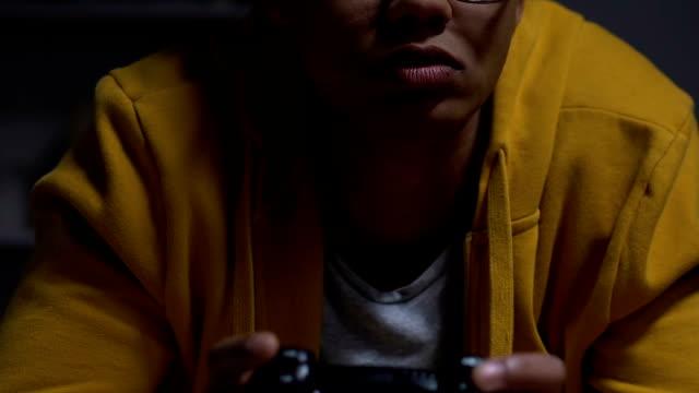vídeos de stock e filmes b-roll de afro-american teenager playing video games at night, bad sleep schedule, health - man joystick