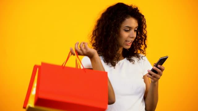 아프리카계 미국 흑인 여 자가 들고 쇼핑백 및 스마트폰, 온라인 구매 - black friday 스톡 비디오 및 b-롤 화면