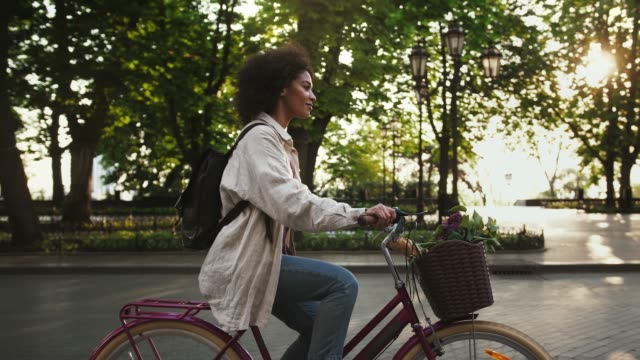 Afro-american woman riding a bicycle with flowers and baguette in basket by deserted city avenue next to an alley with green trees. Slow motion