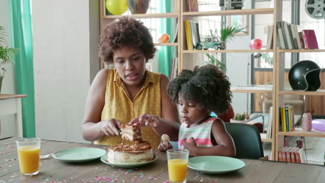Afro-Caribbean Mother Cutting and Serving Birthday Cake for Daughter