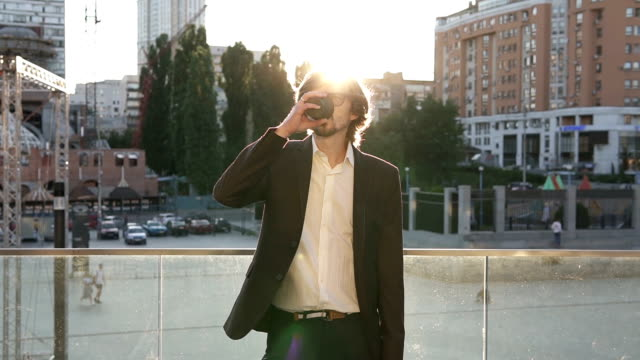 after a hard day at work, a businessman drinks coffee at sunset. big city brings a lot of money - кофе брейк стоковые видео и кадры b-roll