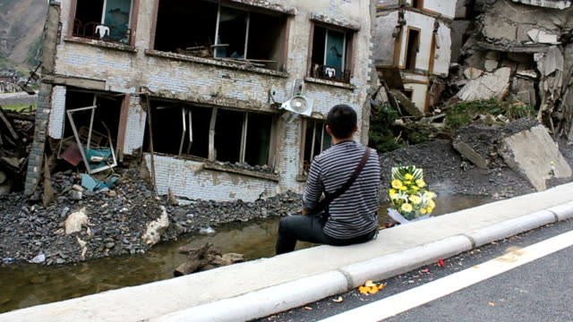 After earthquake a man is in deep mourning for his family in the house ruins which were destroyed by 2008's earthquake in Sichuan Province,China.  earthquake stock videos & royalty-free footage