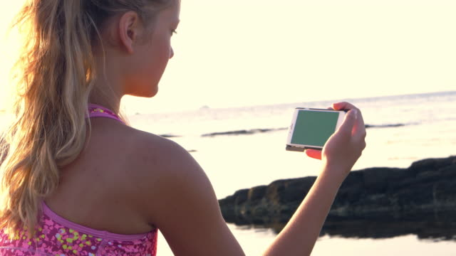 After rocky shore training. Girl checking on her smart phone with green screen