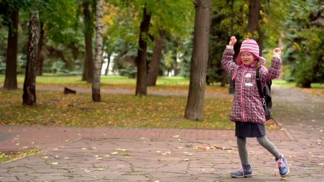 dopo aver studiato a scuola. studentessa con gli occhiali che ballano nel parco. minuto di riposo nel parco dopo la scuola. rallentatore. - berretto video stock e b–roll