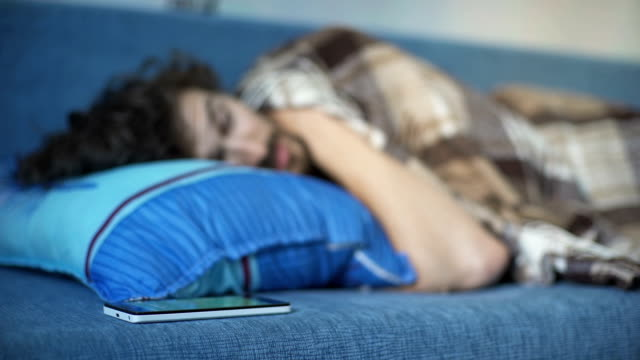 efter utlösa larmet på telefonen vaknar den sovande mannen - alarm clock bildbanksvideor och videomaterial från bakom kulisserna