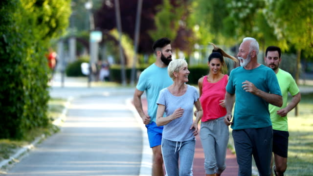 Afternoon Jogging Closeup front view of group of mixed age people having a light jogging at a local park on a sunny summer afternoon.  There are two seniors and three mid 20's people. 4k athleticism stock videos & royalty-free footage