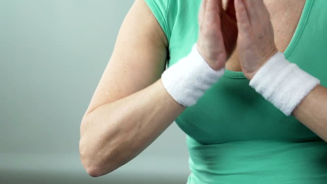 Aged female putting palms one against another in yoga lotus position, hobby video